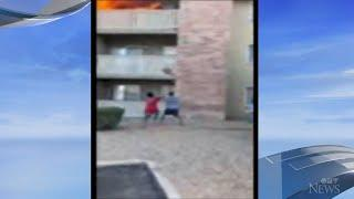 Watch: Man makes life-saving catch as mother throws young son from burning balcony in Arizona.